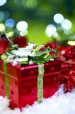 Christmas Presents. Presents Sharing Holiday Photo Theme. Small Red Christmas Boxes with Green Bows. Cool Green Bokeh and Fake Snow Royalty Free Stock Photography
