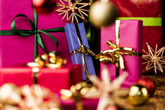 Christmas Presents amidst Baubles and Stars. Single-colored Xmas gifts in magenta, crimson and blue with bow knots. Shallow depth of field. Focus is on the Stock Photos