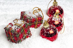 Christmas presents and baubles in the snow Royalty Free Stock Photography