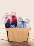 Christmas presents and baubles in a wooden woven basket Royalty Free Stock Image