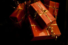 Christmas presents on black. A collection of x-mas presents in red gift wrap paper and golden ribbons on a black background royalty free stock photo