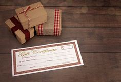 Christmas Presents and Blank Gift Certificate. On a Wooden Table royalty free stock photo