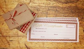 Christmas Presents and Blank Gift Certificate. On a Wooden Table royalty free stock photography