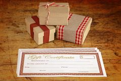 Christmas Presents and Blank Gift Certificate. On a Wooden Table royalty free stock photos
