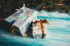 Christmas presents on blue wooden table with fir sprigs. And Christmas lights royalty free stock photography