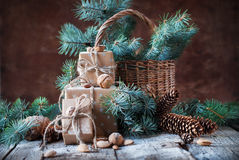 Christmas Presents. Boxes, Coniferous, Pine Cones, Fir Tree, Basket, Walnuts, Almonds on Dark Wooden Background Stock Image