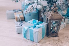 Christmas gifts under the Christmas tree. Christmas presents in boxes lie near the decorated Christmas tree Royalty Free Stock Image