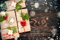 Christmas presents in boxes on a wooden background with copy space. Drawn snowfall. Royalty Free Stock Photo