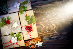 Christmas presents in boxes on a wooden background with copy space. Drawn snowfall. Royalty Free Stock Image