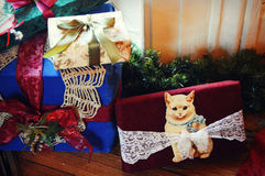 Christmas Presents. Brightly wrapped blue and red Christmas presents with a cat and lace doilies Royalty Free Stock Photography