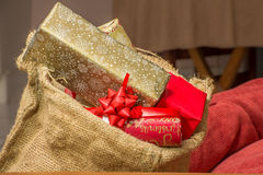 Christmas Presents in Brown Hessian Bag. Christmas presents stacked to the brim inside a brown hessian bag resting near some red pillows inside a home Stock Image