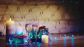 Christmas presents, candles and two glasses of champagne blue garland background. Close up shot of christmas and new year gift boxes, candles and two glasses of stock video footage
