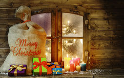 Christmas Presents and Candles at Window Pane Royalty Free Stock Images