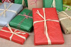 Christmas Presents Closeup. Closeup of a large group of wrapped Christmas presents on a burlap surface. A variety of presents wrapped with tissue paper and plain royalty free stock image