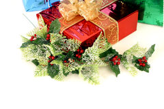 Christmas presents with decor. 3 christmas presents with some holly on a with background Stock Image