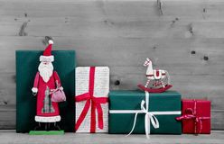 Christmas presents and gift boxes with Santa on grey wooden back Stock Image