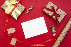 Christmas presents. Gifts packed in craft paper, greeting card letter, bow, dried flowers on red background. Xmas and Happy New Ye. Ar composition. Flat lay royalty free stock photography