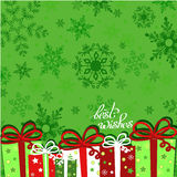 Christmas presents on green  seamless snowflake pattern. Greeting card with message best wishes. Stock Photos