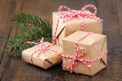 Christmas presents. Group of three Christmas presents wrapped in brown paper and ties with a festive red and and white baker's twine on dark wooden background Royalty Free Stock Photos