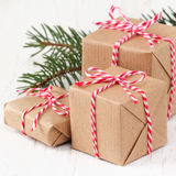 Christmas presents. Group of three Christmas presents wrapped in brown paper and ties with a festive red and and white baker's twine on dark wooden background Royalty Free Stock Photo