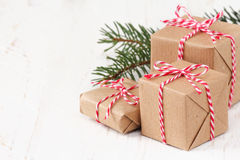 Christmas presents. Group of three Christmas presents wrapped in brown paper and ties with a festive red and and white baker's twine on white wooden background Stock Images