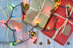 Christmas Presents and Lights. Three tissue wrapped Christmas presents on a rustic white wood table. A string of holiday lights and ornaments are draped over the Royalty Free Stock Images