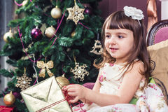 Christmas presents. Little girl in a stylish smart dress unpacks Christmas gifts sitting on sofa next to the comfortable elegant festive Christmas tree. A series Royalty Free Stock Image