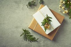Christmas presents with natural evergreen twigs on gray background. Flatlay. Copy space Stock Photo