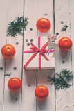 Christmas presents with red ribbon and tangerines Royalty Free Stock Image