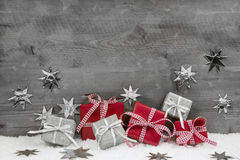 Christmas presents in red and silver on wooden grey background. Christmas presents in red and silver on wooden grey wooden background Royalty Free Stock Photo