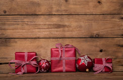 Christmas presents with a red white checked ribbon on old wooden royalty free stock photography