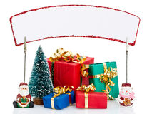 Christmas presents and sign. Wrapped pile of Christmas presents with blank sign, isolated on white background royalty free stock images