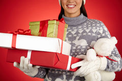 Christmas presents. Smiling female in winterwear holding xmas packages and teddy bear royalty free stock image