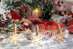 Christmas presents in the snow, snowflakes on clothespins, cheerful snowman and red lantern on the background of New Year`s scener. Y. Christmas and New Year Royalty Free Stock Photo