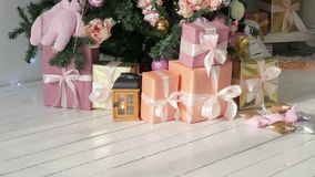 Christmas presents stand under the tree. pink and orange boxes with light ribbons. Christmas presents stand under the tree stock footage
