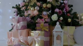 Christmas presents stand under the tree. pink and orange boxes with light ribbons. Christmas presents stand under the tree stock video