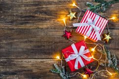 Christmas presents with stars and lights. Christmas background with presents and stars decorations, fir tree branches and lights on wooden board Royalty Free Stock Images