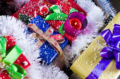 Christmas presents and tinsel. Close up of colorful Christmas presents decorated with tinsel and fake snow, festive scene royalty free stock photography