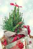 Christmas presents under the christmas tree. On snowy background with snowflakes stock photo