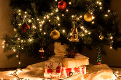 Christmas presents under Christmas tree. Christmas presents under decorated gerlyandoy, bright yellow and red balls Christmas tree royalty free stock photo