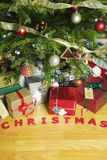 Christmas presents under an Christmas Tree. Christmas presents under an illuminated Christmas Tree royalty free stock photography
