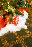 Christmas presents under the tree. Christmas presents under a christmas tree, surrounded by carpet with gold design royalty free stock image