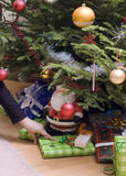 Christmas presents under tree. A hand placing some Christmas presents under a Christmas tree stock photo