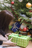 Christmas presents under tree. A woman placing some Christmas presents under a Christmas tree royalty free stock image
