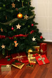 Christmas Presents Under Tree. Gift boxes with golden or red ribbon stock photos