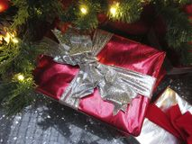 Christmas Presents Under the Tree. Photo of pretty red and silver christmas presents under a tree royalty free stock photos