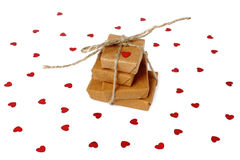 Christmas presents / Valentines day gifts wrapped in brown wrapping paper surrounded by red hearts Royalty Free Stock Images