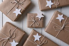 Christmas presents with wood star gift tags. Top view of a group of plain paper wrapped Christmas presents with blank wood star gift tags Royalty Free Stock Image