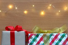 Christmas presents on wooden background with lights. royalty free stock images