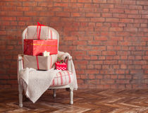 Christmas presents on a wooden floor on a brick wall background. Royalty Free Stock Images